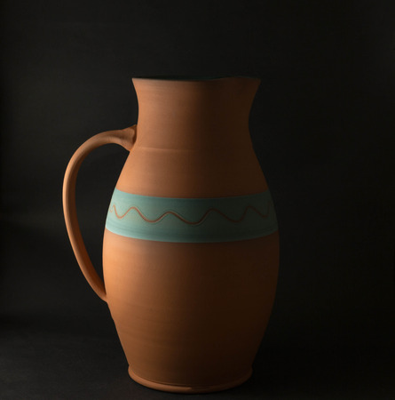 A terracotta jug with a black background.