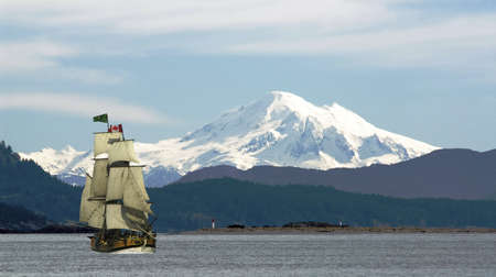 Mount Baker looms over the tall ship Lady Washington off Sidney, on Vancouver Island, British Columbia, Canada