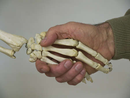 A man shakes hands with a human skeleton as if agreeing on a deal