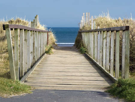 Wooden boardwalk leading to blue sea and beach. Stock Photo