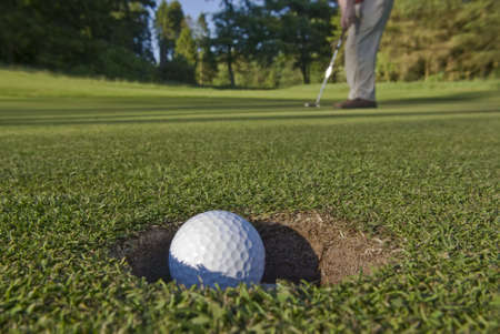 A golfer sinks a long putt and watches the ball dive into the hole.