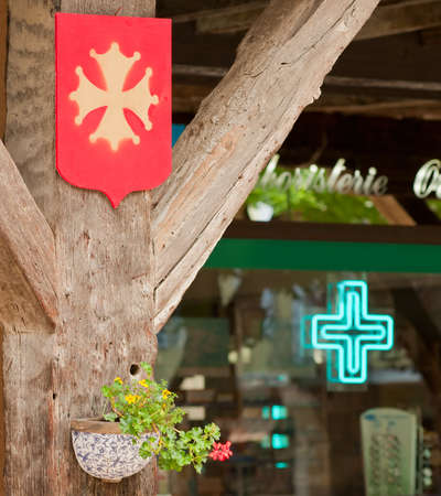 Ancient Cathar cross set against a pharmacy cross in a French village.