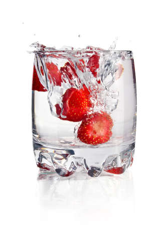 tumbler: splash water in glass with strawberry isolated on white background