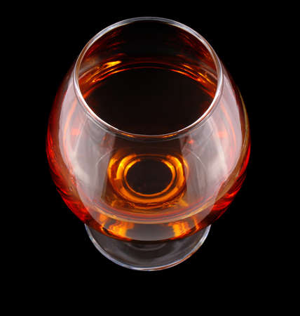spirituous beverages: cognac in goblet isolated on black background