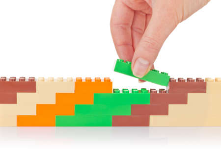 Hand build wall of colour toy block. Isolated on white background Stock Photo