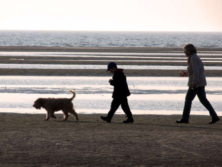 portrait of mother and child with dog walking nearby ocean