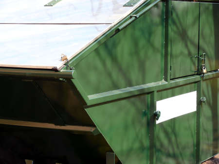 commercial recycling: portrait of locked rubbish skip with white sign for advertise etc. Stock Photo