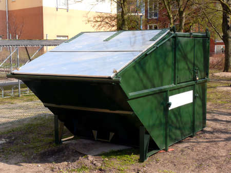 dumpster: portrait of locked rubbish skip with white sign for advertise etc. Stock Photo
