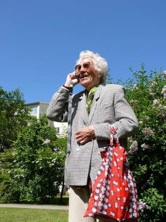 portrait of happy senior woman mobile conversation photo