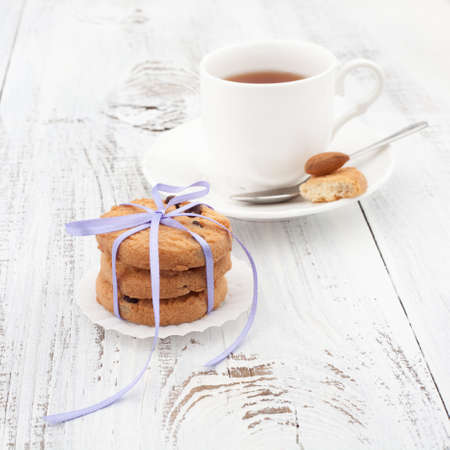 Festive wrapped chocolate homemade cookies with cup of tea on white wooden background photo
