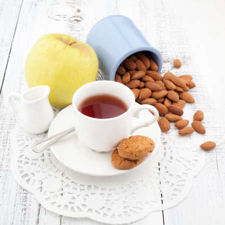 Breakfast with fresh homemade cookies, apple and nuts with cup of tea on wooden table photo