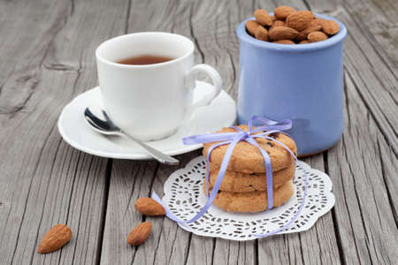 coffee pot: Festive wrapped chocolate homemade cookies and almond with cup of tea on wooden background