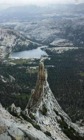 View from Cathedral Peak, the lightning rod of Yosemite National Park with a stunning view overlooking the landscape and a storm coming. Pinnacle in the foreground