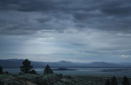 Storm coming in over a cold lonely landscape with a lake and a few sun-beams coming through the clouds