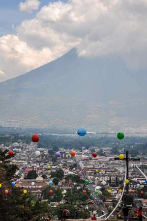 Distant view of the Volcano El Fuego o Acatenango with cross in the foreground in Antigua, Guatemala Stock Photo