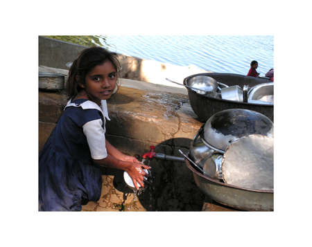 Ahmedabad, Gujarat, India - December 7, 2005 year. The girl helps wash the pots. Working children in India. Stock Photo - 13668930