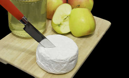 composition of apples, cheese and honey with a knife on a black background photo