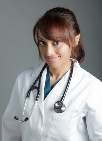 Attractive Indian doctor woman posing in a studio in front of a background photo