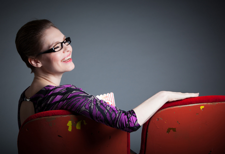 Attractive caucasian woman in the theatre in her 30 isolated on a grey background photo