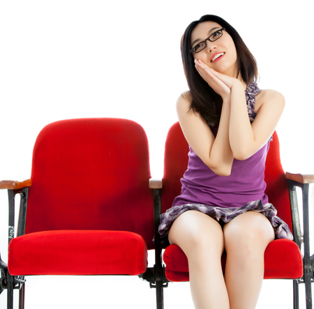 劇場で彼女の 20 代の魅力的なアジアの女の子が白の背景に分離します。