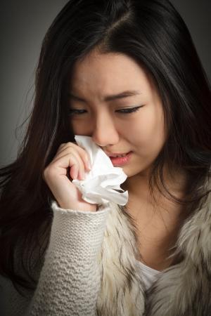 mujer llorando: Muchacha asiática atractiva en su veintena aislados sobre un fondo plano plein en un estudio