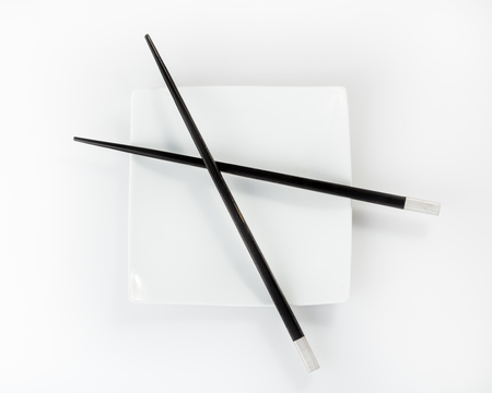 chopsticks on a plate isolated on a white background Imagens - 22598391