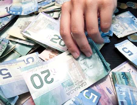 canadian currency: Persons hands picking Twenty Canadian Dollar Bill from heap of paper currency
