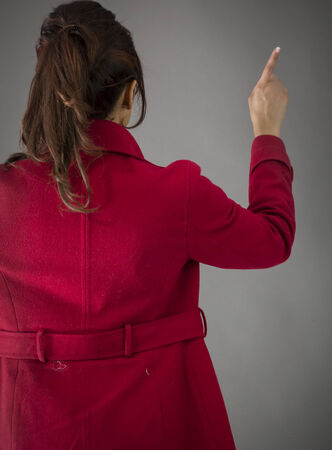 Rear view of an Indian young woman pretending to work on touch screen photo