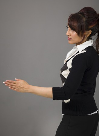 Indian businesswoman giving hand for handshake isolated on colored background photo