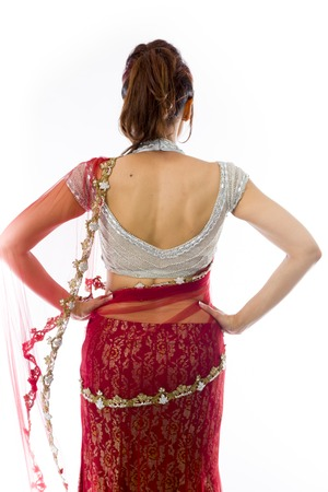 Rear view of a young Indian woman standing with her arms akimbo