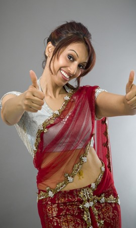 Smiling young Indian woman showing thumb up sign with both hands photo