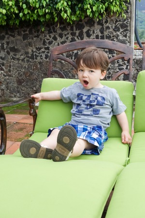 Boy sitting on a lounge chair and yawning