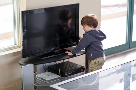 Boy operating a television