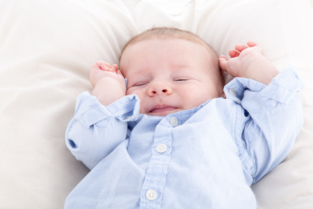baby facial expressions: Baby boy sleeping on the bed Stock Photo