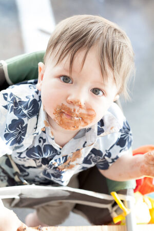 Portrait of a boy with cake all over his face photo