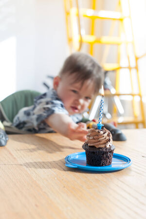 Boy reaching towards a birthday cake photo