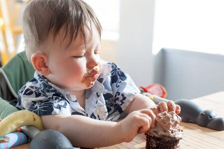 Boy eating a birthday cake photo