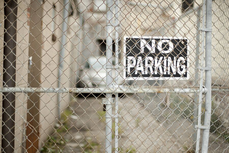 No parking sign behind chainlink fence photo