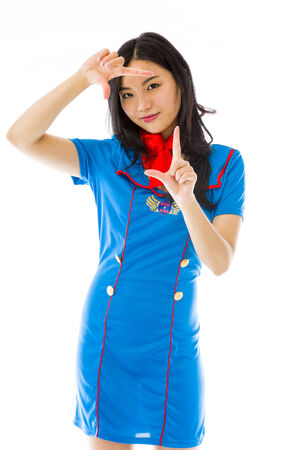 Asian air stewardess looking through finger frame photo