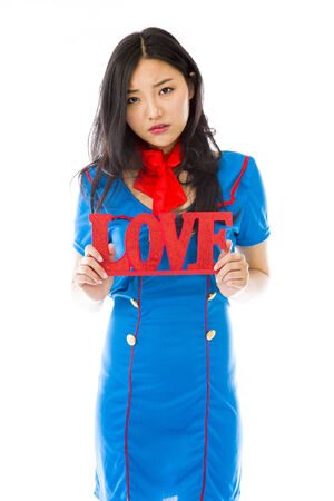 Disappointed Asian air stewardess holding red LOVE text