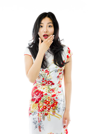 Shocked Asian woman with hand over mouth isolated on white background photo
