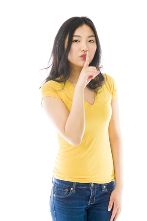 speak out: Young Asian woman standing with finger on lips Stock Photo