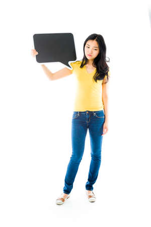 Upset Asian young woman holding a blank speech bubble