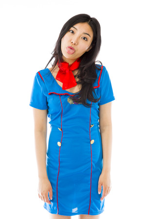 misbehaving: Asian air stewardess poking out tongue towards camera isolated on white background
