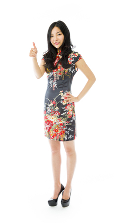 Asian young woman making thumbs up sign standing with hand on hip photo