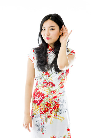 sensory perception: Asian young woman with hand to ear listening isolated over white background Stock Photo