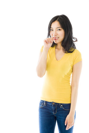 Young Asian woman smiling with finger in mouth photo
