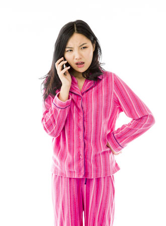 Young Asian woman talking on a mobile phone and looking confused photo