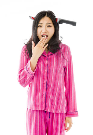 Scared Asian young woman wearing knife shaped hair band photo
