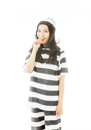 Young Asian woman smiling in prisoners uniform with finger in mouth photo